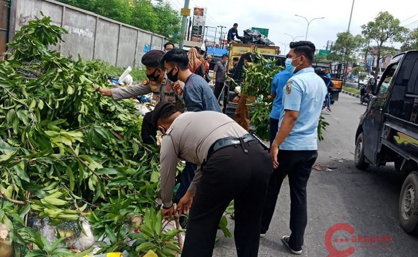Petugas kepolisian ikut mengangkuat tumpukan sampah.